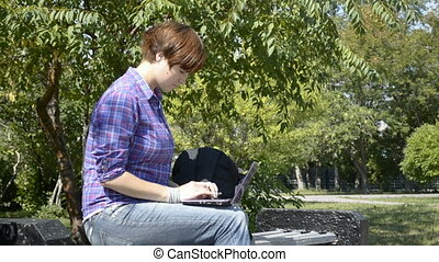 A young woman uses a laptop