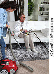 a young woman vacuuming at a senior woman's home
