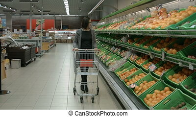 A young woman visiting ? supermarket