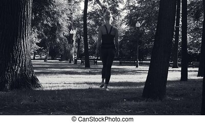 A young woman walking barefoot on the grass