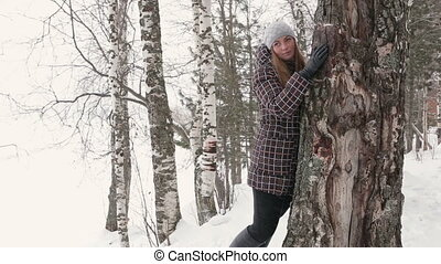 A young woman walking in winter forest and hugging a tree....