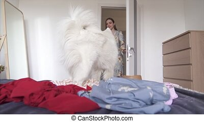 A young woman walks into the room where the pet made a mess....