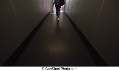 A young woman walks on a dark gangway after a plane lands. ...