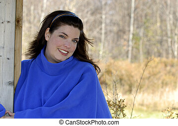 Outdoors - A Young Woman Wearing A Bright Blue Poncho...