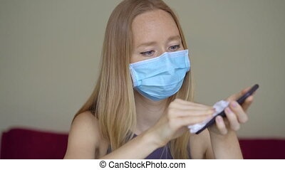 A young woman wearing a face mask works from home during coronavirus self-isolation. She uses an alcohol sanitizer to disinfect her phone