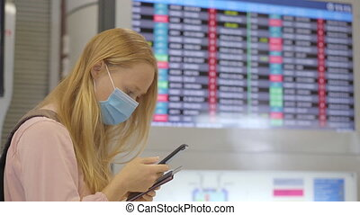 A young woman wearing a medical face mask in an airport ...