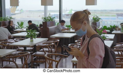 A young woman wearing a medical face mask in an airport stands in a hall with a cellphone in her hands. The concept of the New normal of people's lifestyle. Air travel in the age of Covid-19