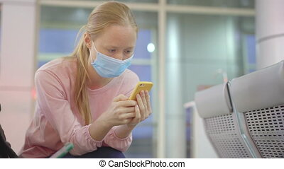 A young woman wearing a medical face mask sits on a chair in an airport using a cellphone. The concept of the New normal of people's lifestyle. Air travel in the age of Covid-19.