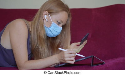A young woman wearing a medical face mask works from home during coronavirus self-isolation. Self-developing during social isolation. A woman draws on a tablet. Working remotely concept