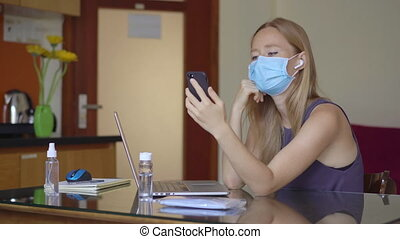 A young woman wearing a medical face mask works from home during coronavirus self-isolation. She talks to someone using a cellphone. Working remotely concept