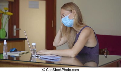 A young woman wearing a medical face mask works from home during coronavirus self-isolation. Working remotely concept