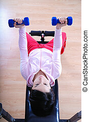 .a young woman weightlifting at gym