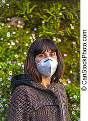 A young woman with a mask next to a beautiful daisies. First walks of the uncontrolled Covid-19 pandemic