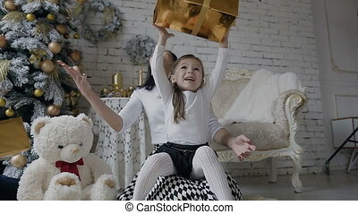 A young woman with a small child sits on a floor near a Christmas tree in a bright spacious room and rejoice in gifts in golden boxes. White the toy bear sits on the floor near the Christmas tree