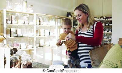 A young woman with a toddler boy buying groceries in zero...