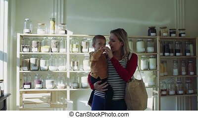 A young woman with a toddler boy in zero waste shop,...