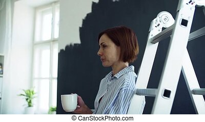 A young woman with coffee painting wall black. A startup of...