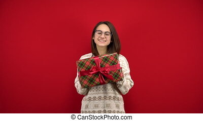 A young woman with glasses shakes a Christmas present in her hands and rejoices. Shooting in the studio on a red background. 4k