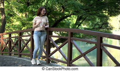 A young woman with glasses stands on a bridge in the park and drinks cold coffee. In the background there is a lake. 4k