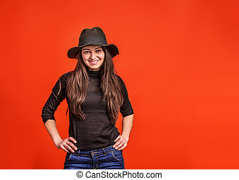 A young woman with hat in studio on a red background.
