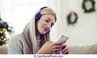 A young woman with headphones and smartphone at home at...