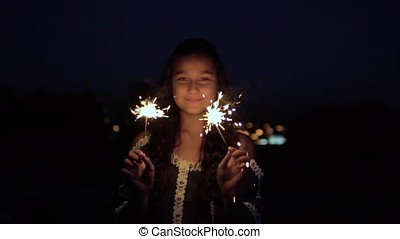 A young woman with long dark hair holds fireworks at night in the background of the city and is happy to have a good mood. slow motion. Portrait