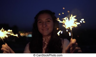 A young woman with long dark hair holds fireworks at night in the background of the city and is happy to have a good mood. slow motion. Portrait. 4K