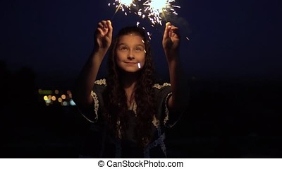 A young woman with long dark hair holds fireworks at night on the background of the city and rejoices. slow motion.