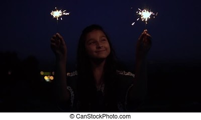 A young woman with long dark hair holds fireworks at night on the background of the city and rejoices. slow motion. HD