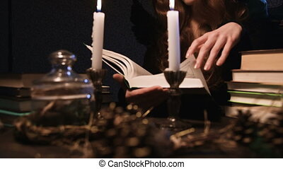 A young woman with long golden hair in a hood dressed in a witch costume by candlelight in a dark room leafing through a thick book. Halloween.
