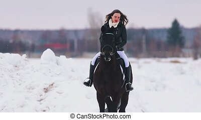 A young woman with long hair and red lipstick riding a horse...