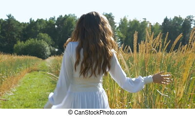 A young woman with long hair in a white dress is walking along the field with wheat.