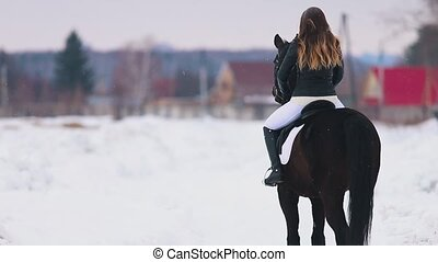 A young woman with long hair riding a horse in a village....