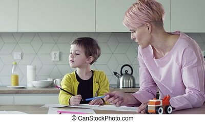 A young woman with small daughter drawing in a kitchen. - A...