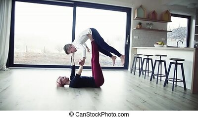 A young woman with small son playing on the floor, having...