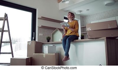 A young woman with tablet planning when moving in new home.