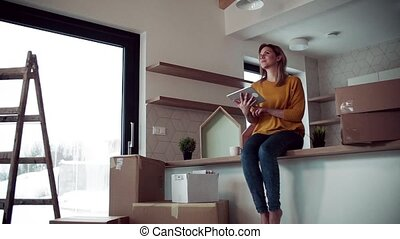 A young woman with tablet planning when moving in new home....