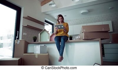 A young woman with tablet planning when moving in new home. Slow motion.