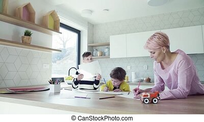A young woman with two children drawing in a kitchen. Slow...