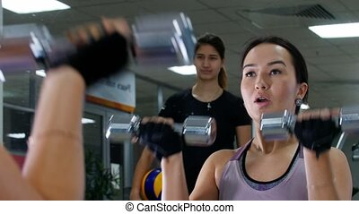 A young woman working out with dumbbells in front of the mirror. Being watched by trainer