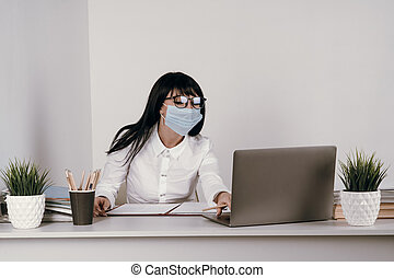 A young woman works remotely in the office with a protective mask during an epidemic.
