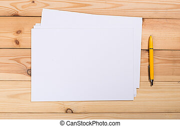 A4 white paper with pen on wooden background. Blank branding template. Photo blank form. Layout for portfolio design.