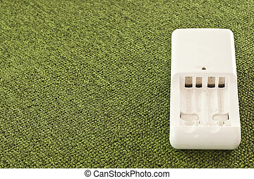 Aa battery charger on a green background.