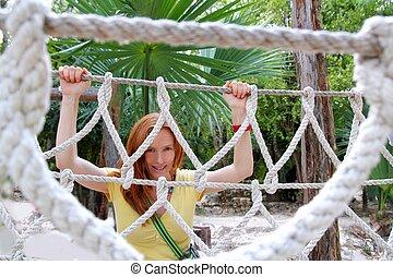 aadventure woman on jungle rope bridge