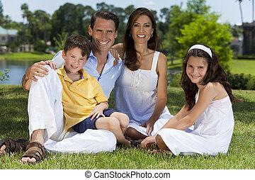 aantrekkelijk, gezin, zitting op het gras, buiten, in, zonneschijn