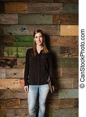 aantrekkelijk, jonge vrouw , staand, tegen, een, houten muur, in, kantoor