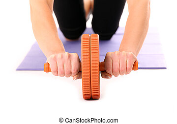 AB wheel - A close-up of a young woman training with AB...