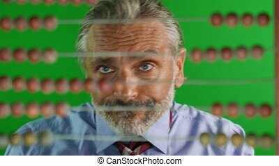 abacus count man - out of focus man behind old abacus,...