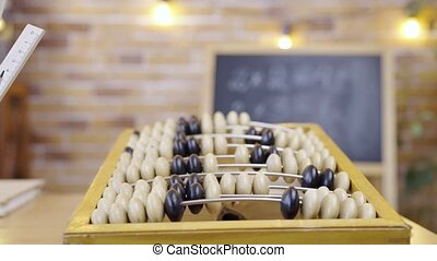 Abacus on the background of an empty school class with chalkboard, close up. School, home education, distance learning. Schooling of arithmetic in elementary school. Studying in primary grades, first lesson, school knowledge.