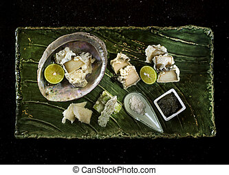 Abalone tempura with black sauce, lemon and salt on wooden tray in black background